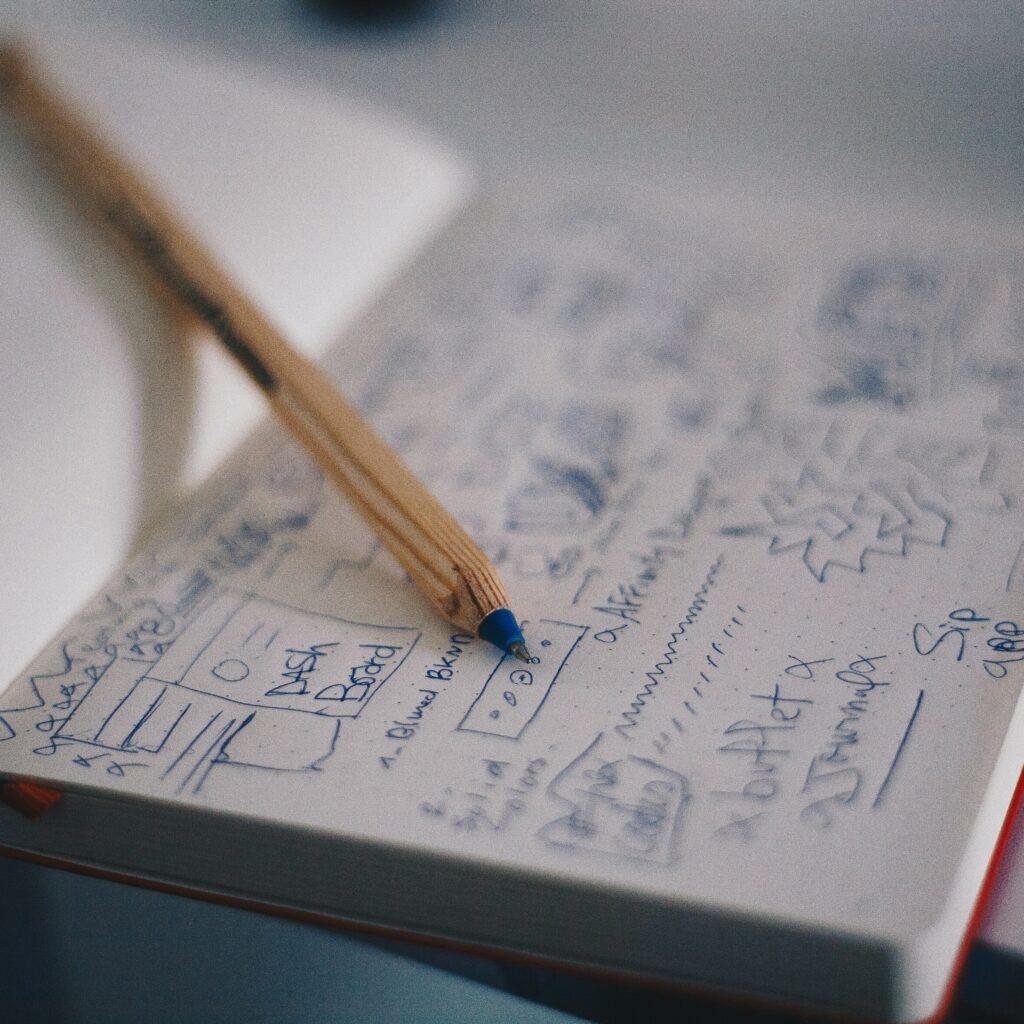 Un cuaderno con muchas anotaciones y un boligrafo, representando a un cuaderno usado por creadores de empresas en Colombia.