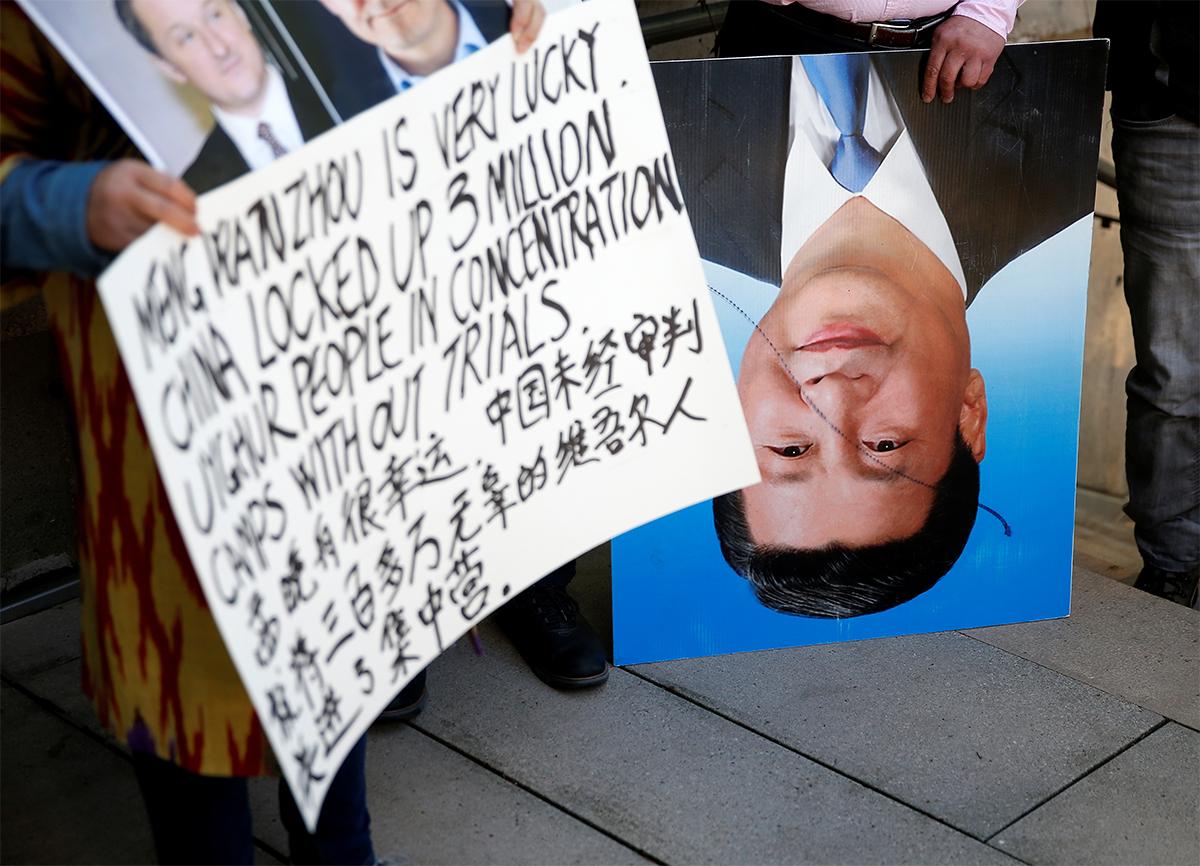 圖/加拿大卑詩省最高法院審理孟晚舟案,庭外示威者手持抗議海報和臉部被劃線的習近平海報,抗議中國迫害新疆維吾爾人。(REUTERS / Lindsey Wasson / 達志影像)
