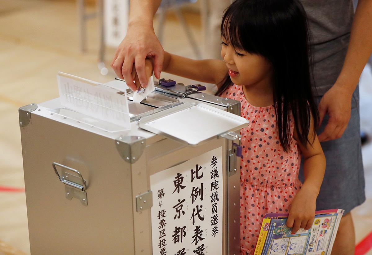 圖/協助父親將選票投入票匭的日本小女孩。(REUTERS / Issei Kato / 達志影像)