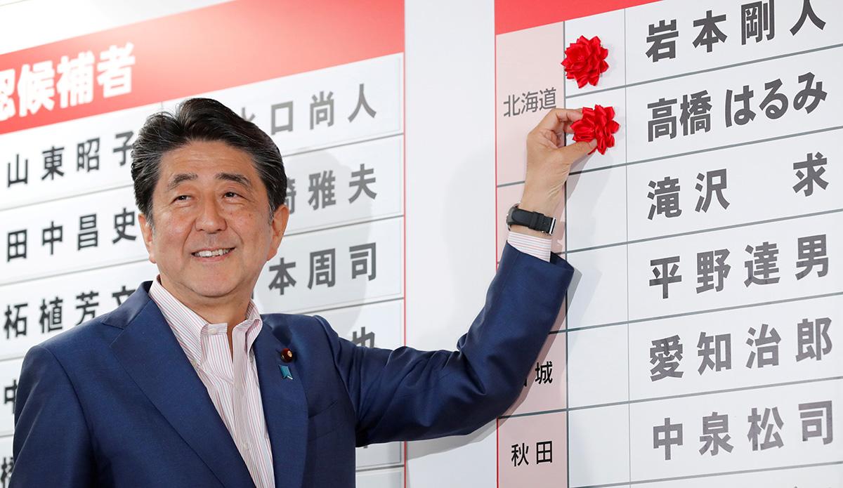 圖/自民黨黨魁安倍晉三將紅花飾貼在準當選人名前。(REUTERS / Kim Kyung-Hoon / 達志影像)