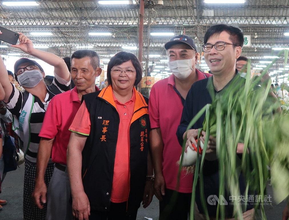 民進黨高雄市長補選參選人陳其邁(前右)19日啟動競選模式,一早就到十全果菜市場拜票,攤商熱情歡迎,並送上好彩頭及蒜苗。