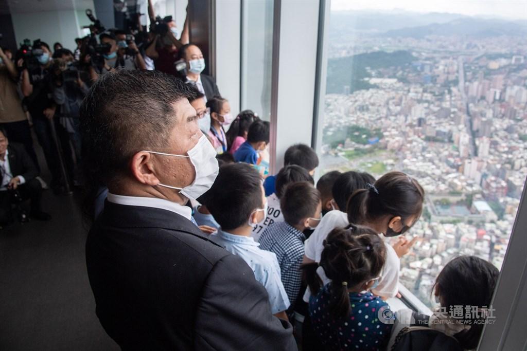 台灣7日正式迎來解封日,衛福部長陳時中(前左)與一群國小、幼稚園的兒童共同參與台北101觀景台導覽服務。