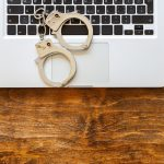 Handcuffs on a laptop, wooden office desk background, top view.