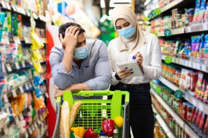 Muslim Family Couple Calculating Prices On Grocery Shopping In Supermarket