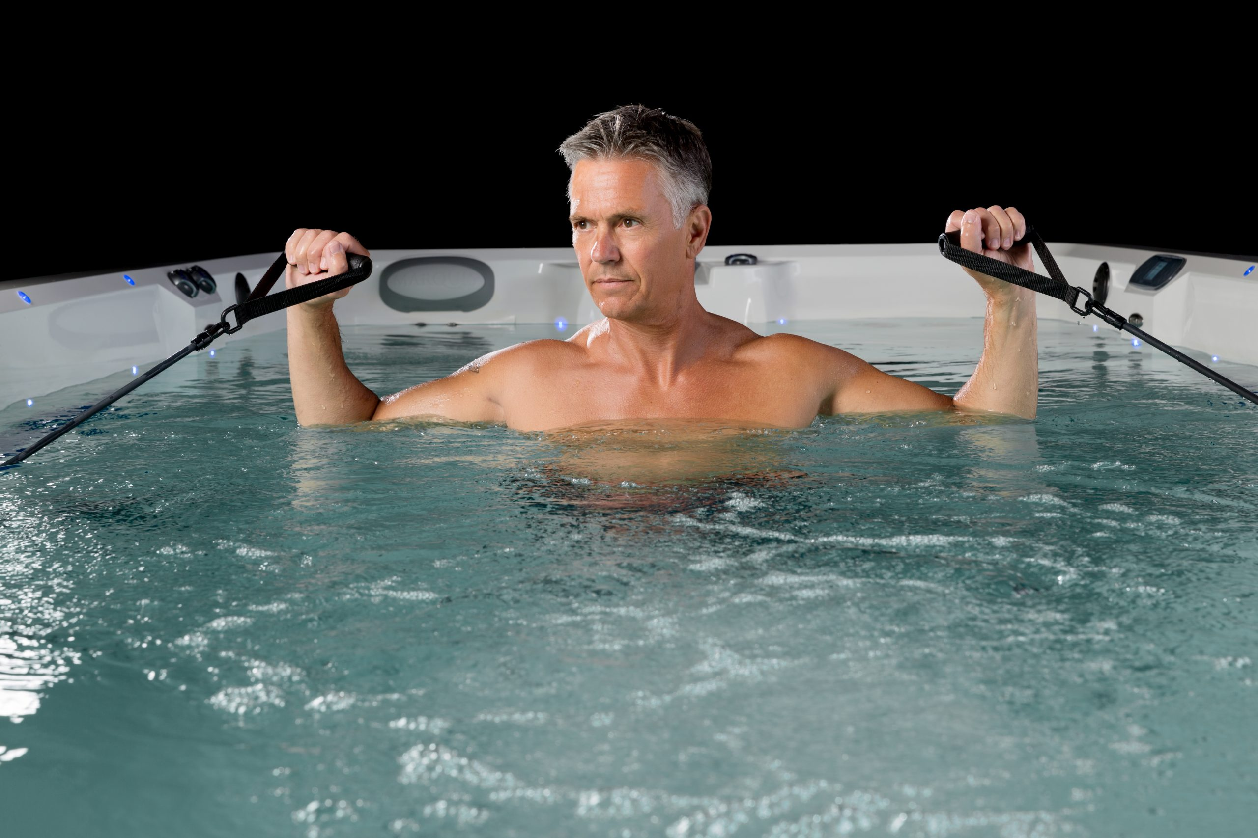 Older male athlete stays fit after 50 with a swim spa