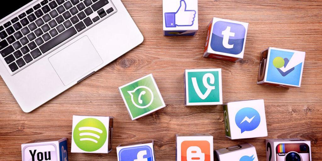 A laptop near different social media platform logos