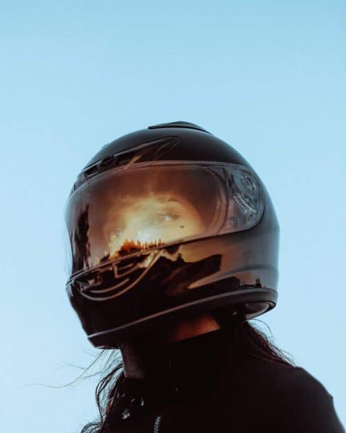 Female Motorcyclist Watching the Sunrise against the Blue Clouds