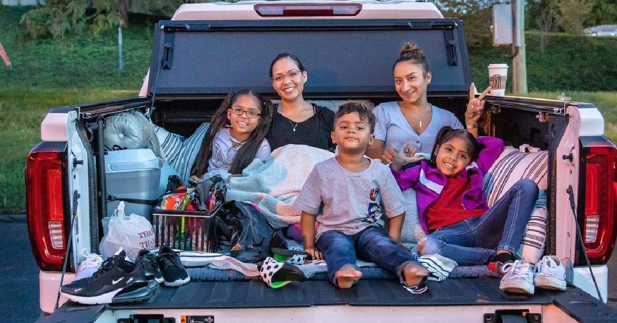 Family in back of pink pick up truck for a drive in movie.