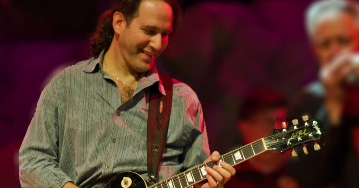 Michael Tash playing guitar on stage.