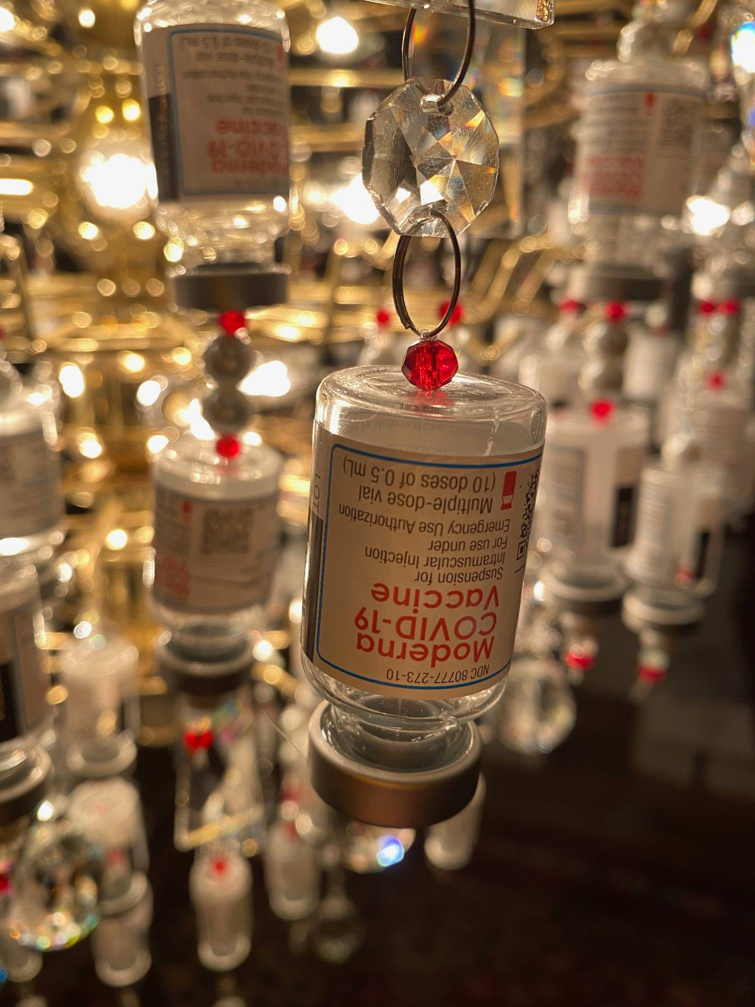"""A close-up look at one of the Moderna vials that makes up the """"Light of Appreciation"""" chandelier made by Laura Weiss."""