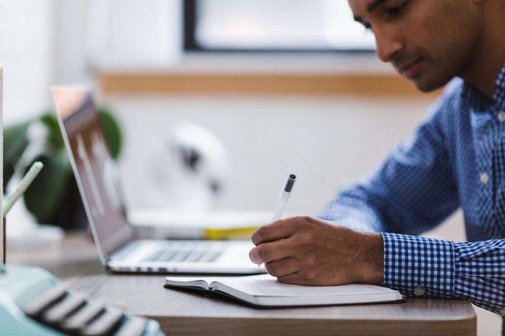 Homem de blusa social azul estudando com um computador, caneta e caderno