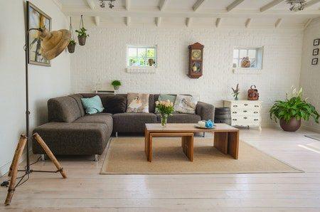 Gulvlampe ved siden af sofa med chaiselong i grå