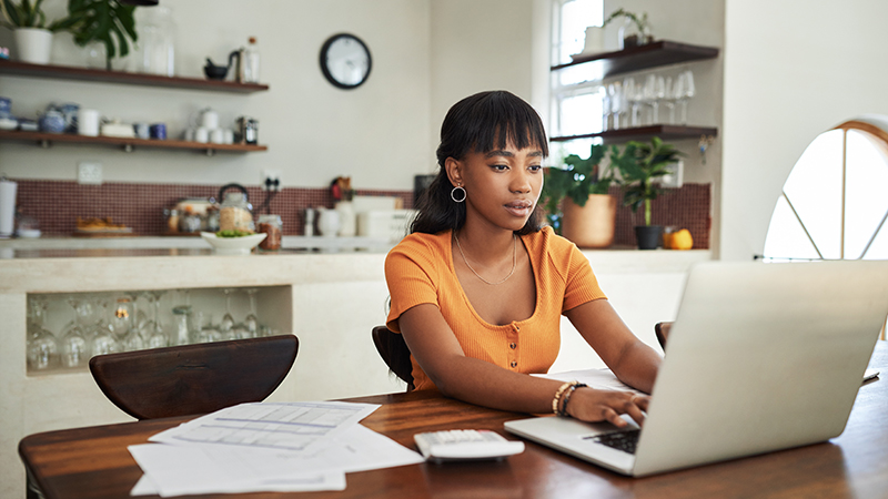 Young woman with financial information and laptop