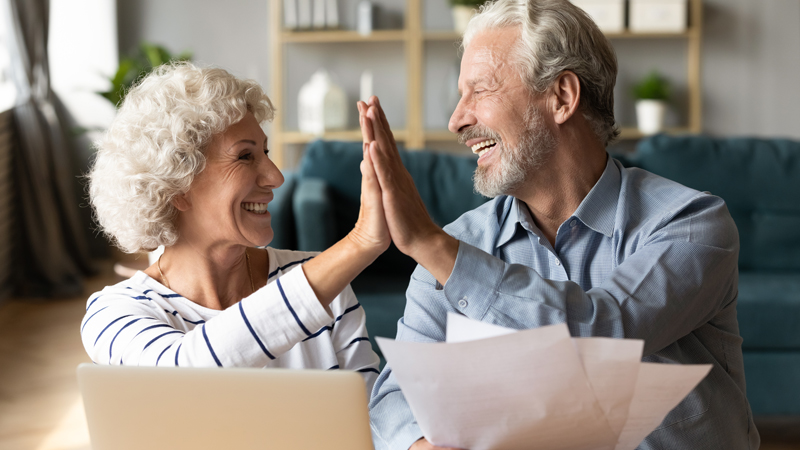 Retired couple high fiving