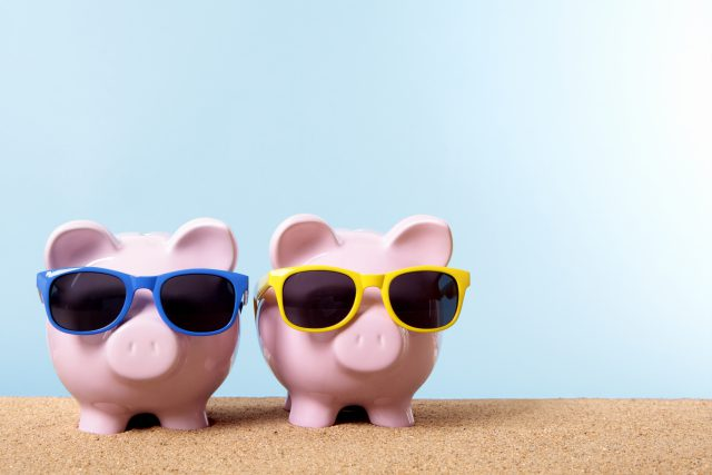Two pink piggy banks on a beach with sunglasses. Space for copy.