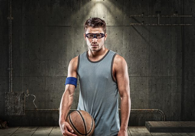 young man on dark background holding basketball ball