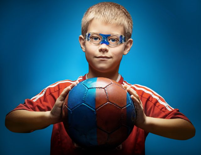 Cute boy is holding afootball ball made of genuine leather isolated on awhite background. Soccer ball
