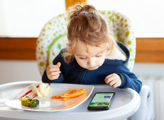 Toddler eats in the high chair while watching movies on the mobile phone. Many children do not want to eat if they do not watch the mobile device or the television.