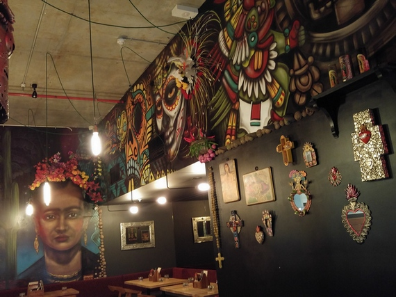 Sin Vida. The walls, decorated with vibrant murals. Frida Kahlo looks down at you as well.