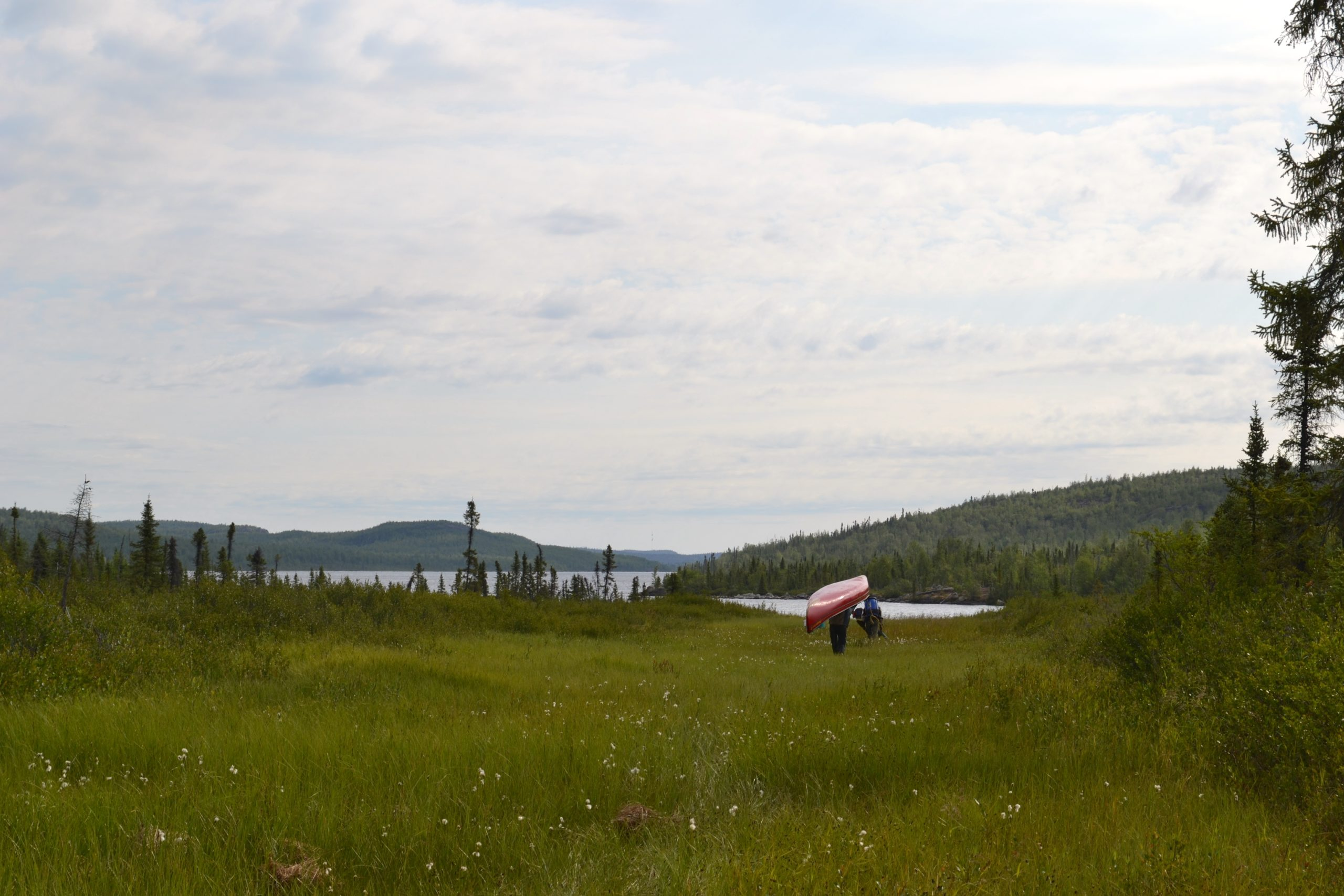 person carrying a canoe in northern canada