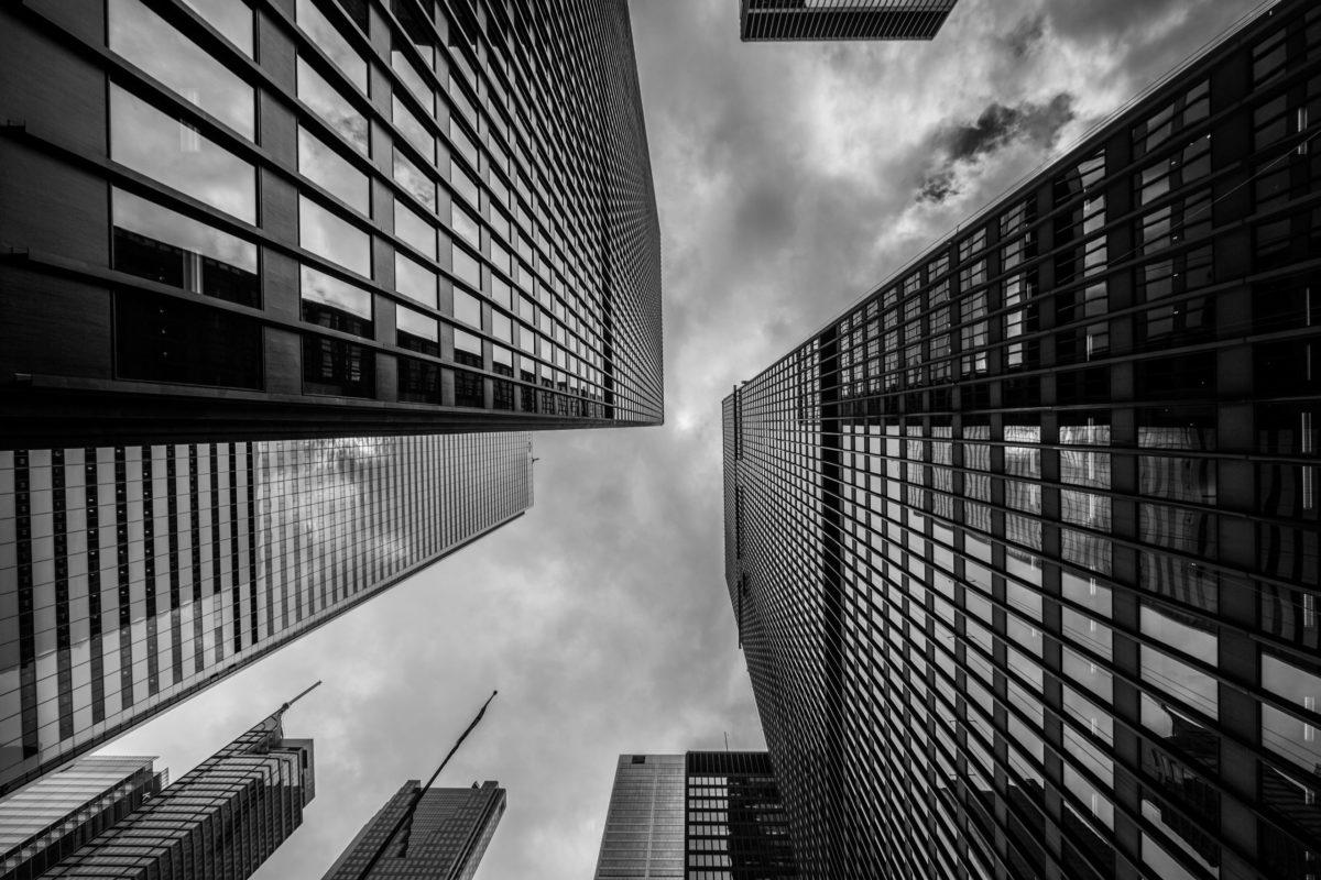 Windowed City Skyscraper Architecture Beneath Cloudscape in Black and White