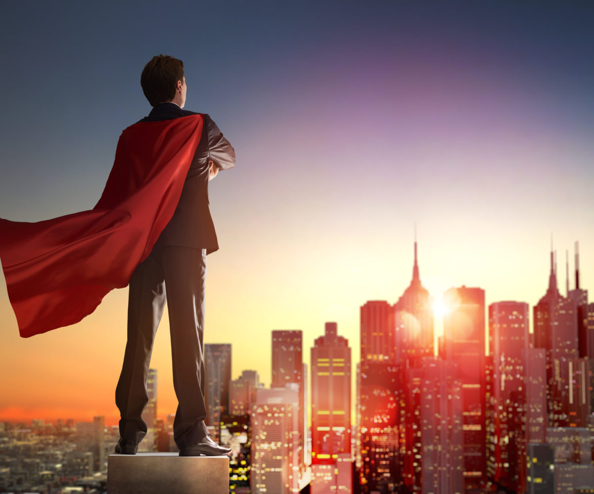 superhero businessman looking at city skyline at sunset. the con