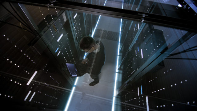Top View Through the Glass of IT Engineer Working with Laptop in Data Center Full of  Active Rack Servers.
