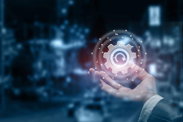 A male hand with an update cogwheel inside a digital sphere.