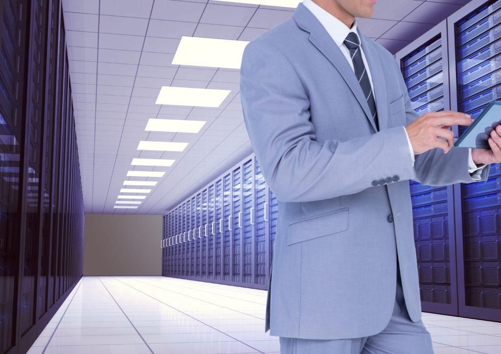 Businessman using digital tablet against server room background