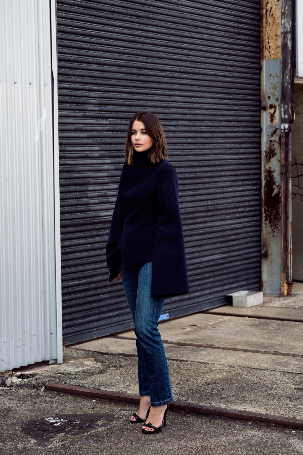 navy blue jacket with extra long sleeves and denim jeans