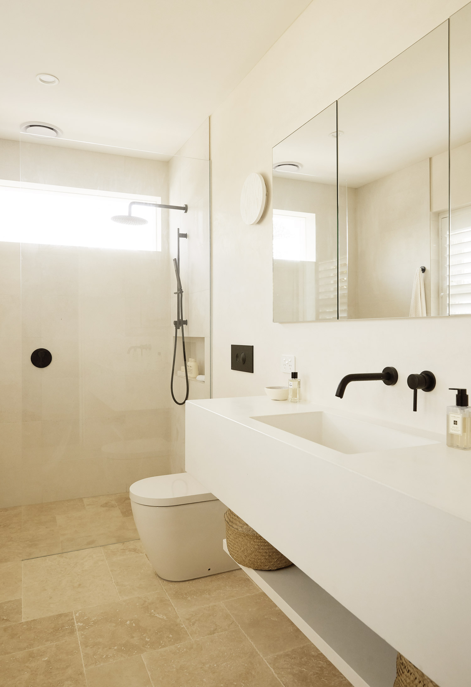 White Concrete sinks, black matte tapware, travertine tiles, Warm minimalist bathroom in Sydney