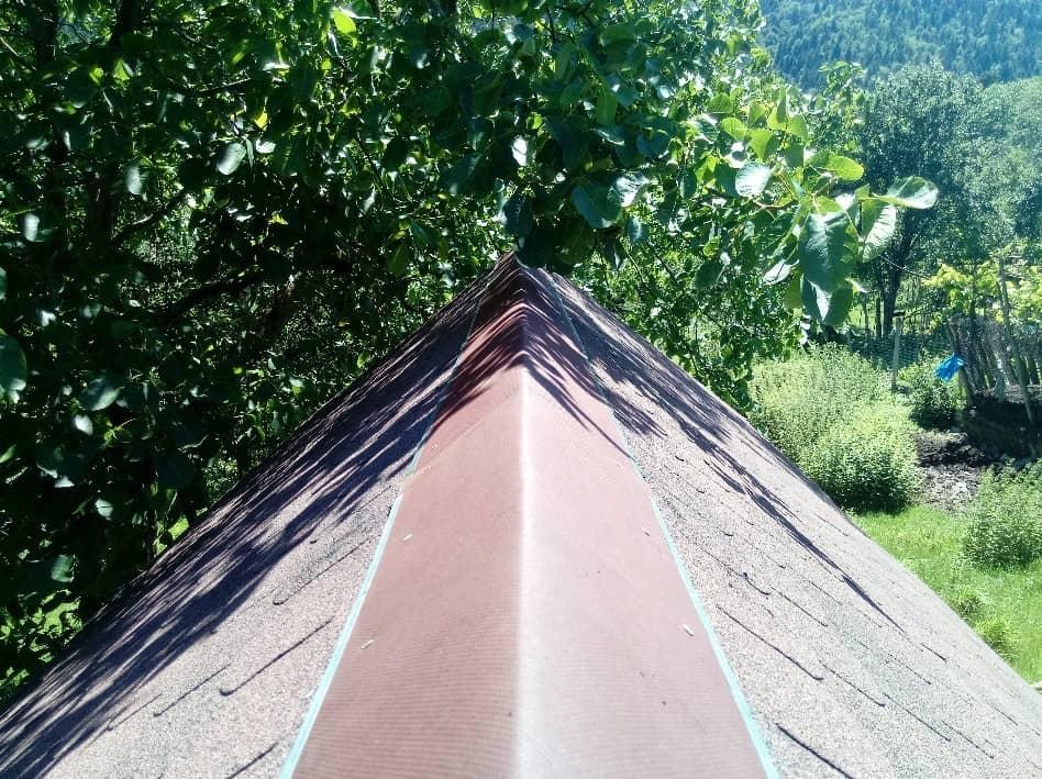 Der Dachfirst mit einer Bitumenschicht unter den Nägeln