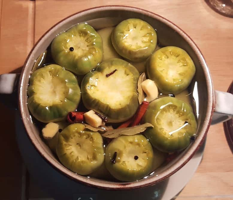 Mit einem Teller beschwert liegen die grünen Tomaten komplett im Sud