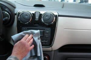 mão limpando painel do carro