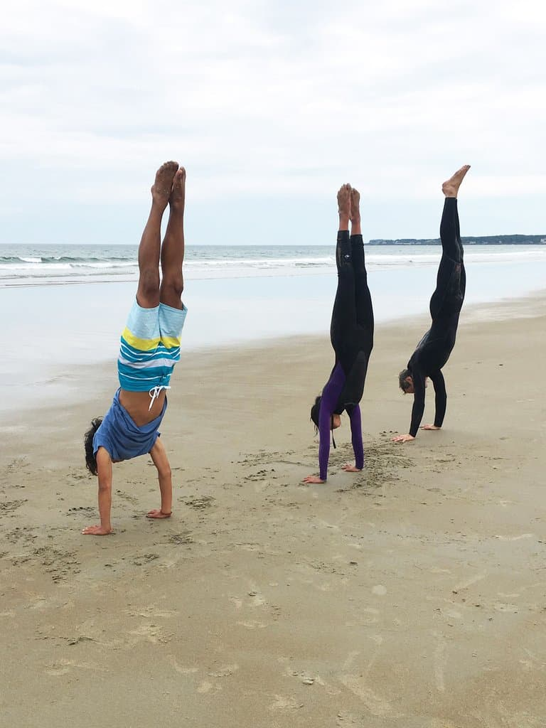 Three people doing hand stands on a beach