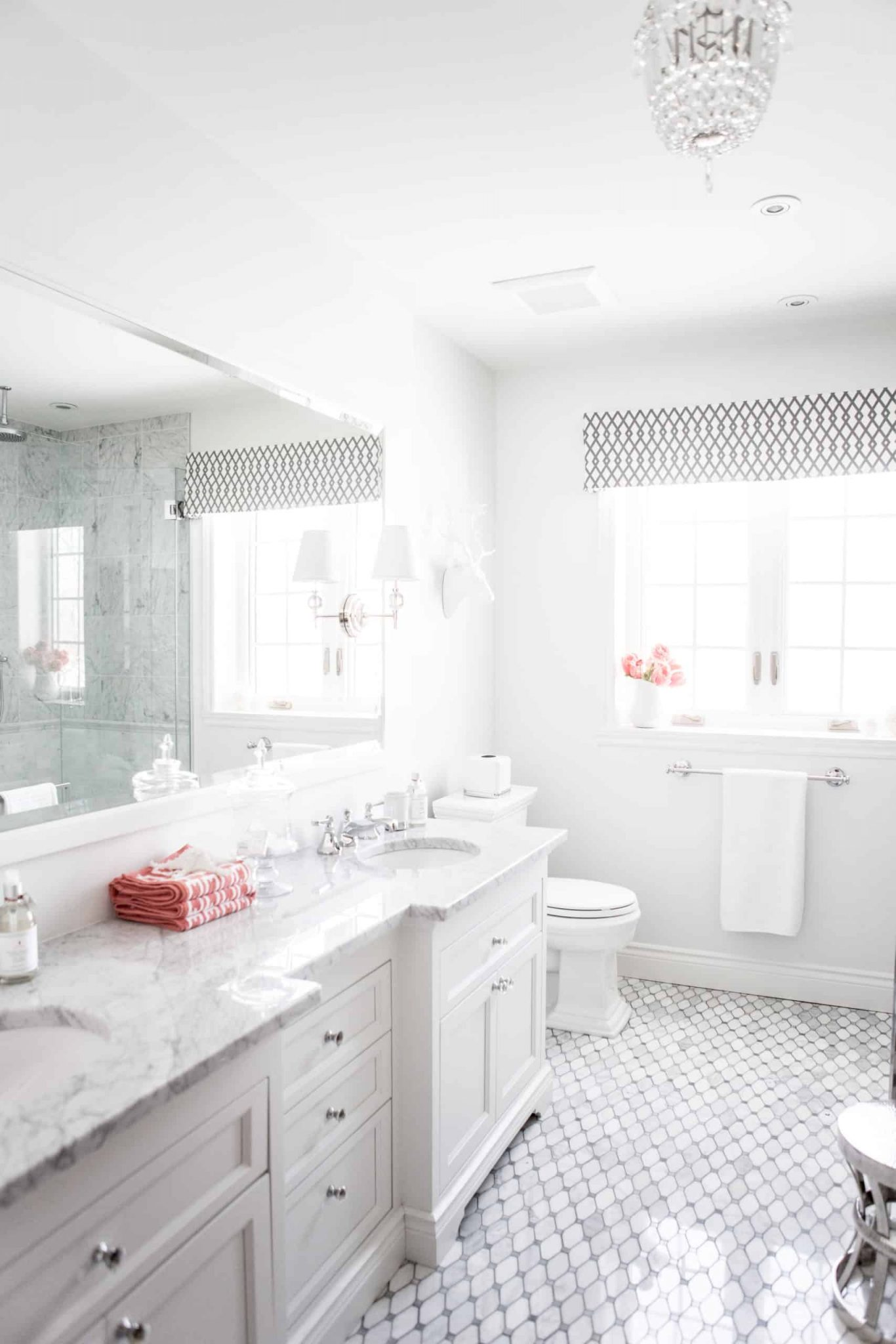 Bright white bathroom with a massive mirror above the double vanity