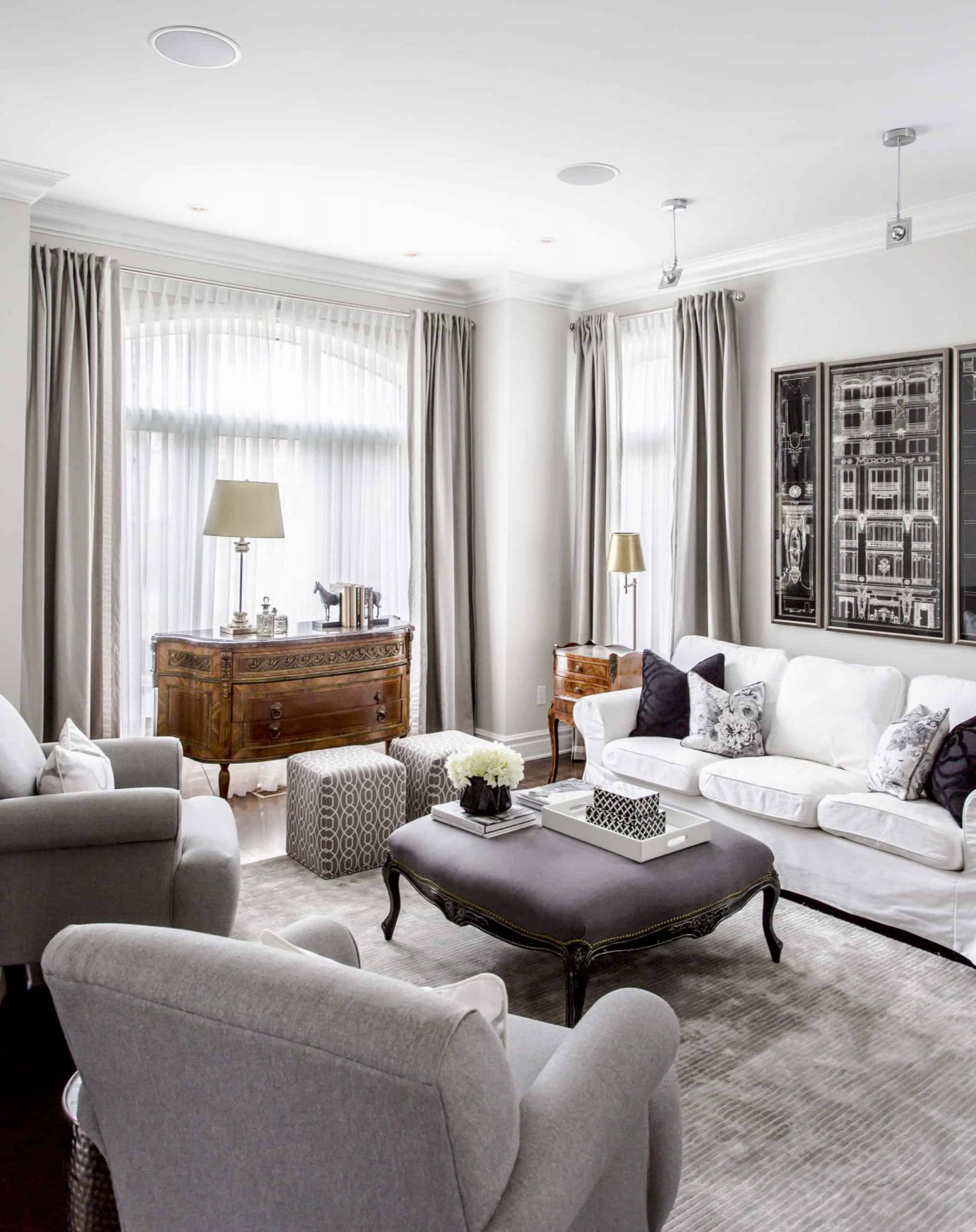 Large, open living room with a picture above the bright white couch