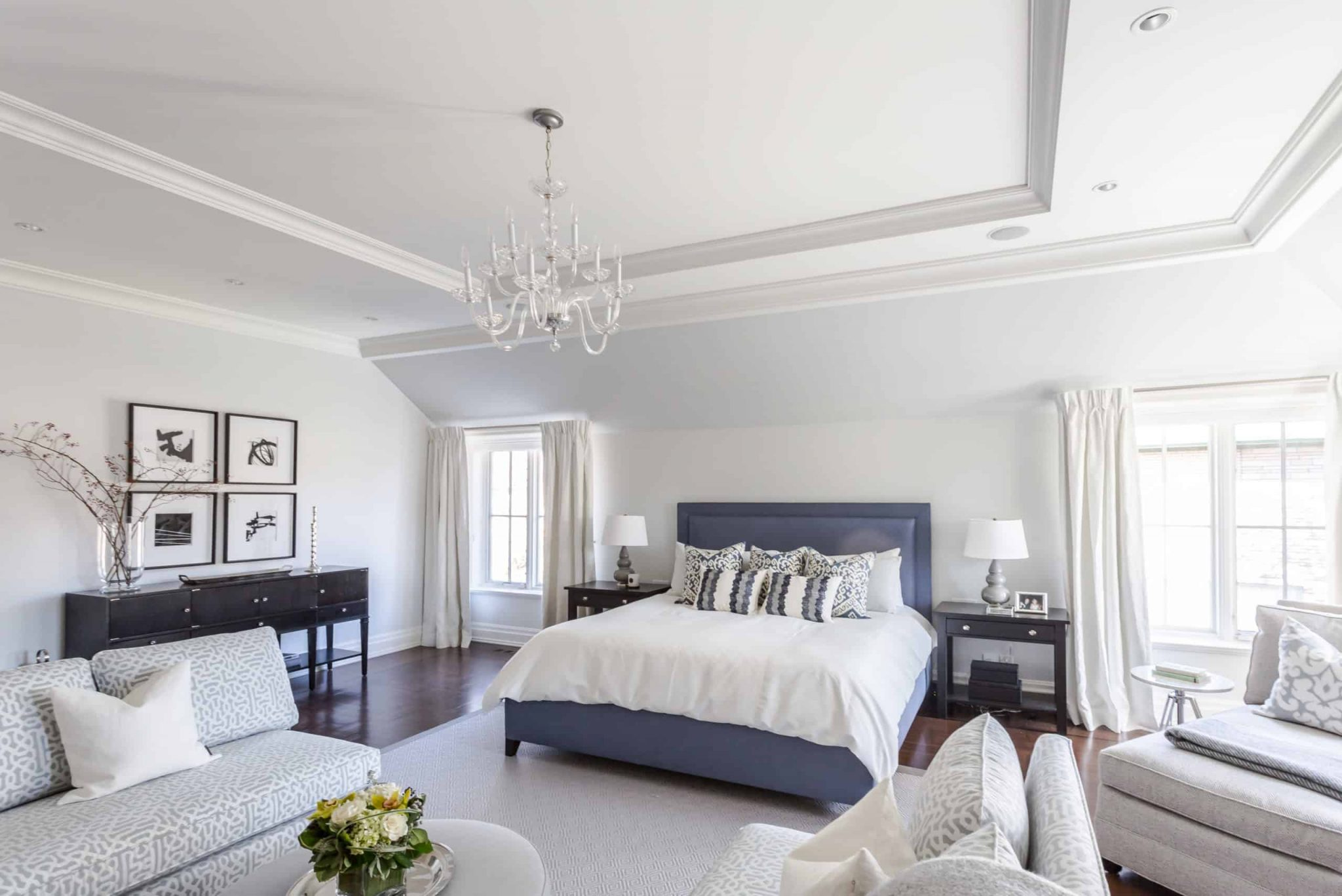 Blue bed with white blankets inside a large bedroom