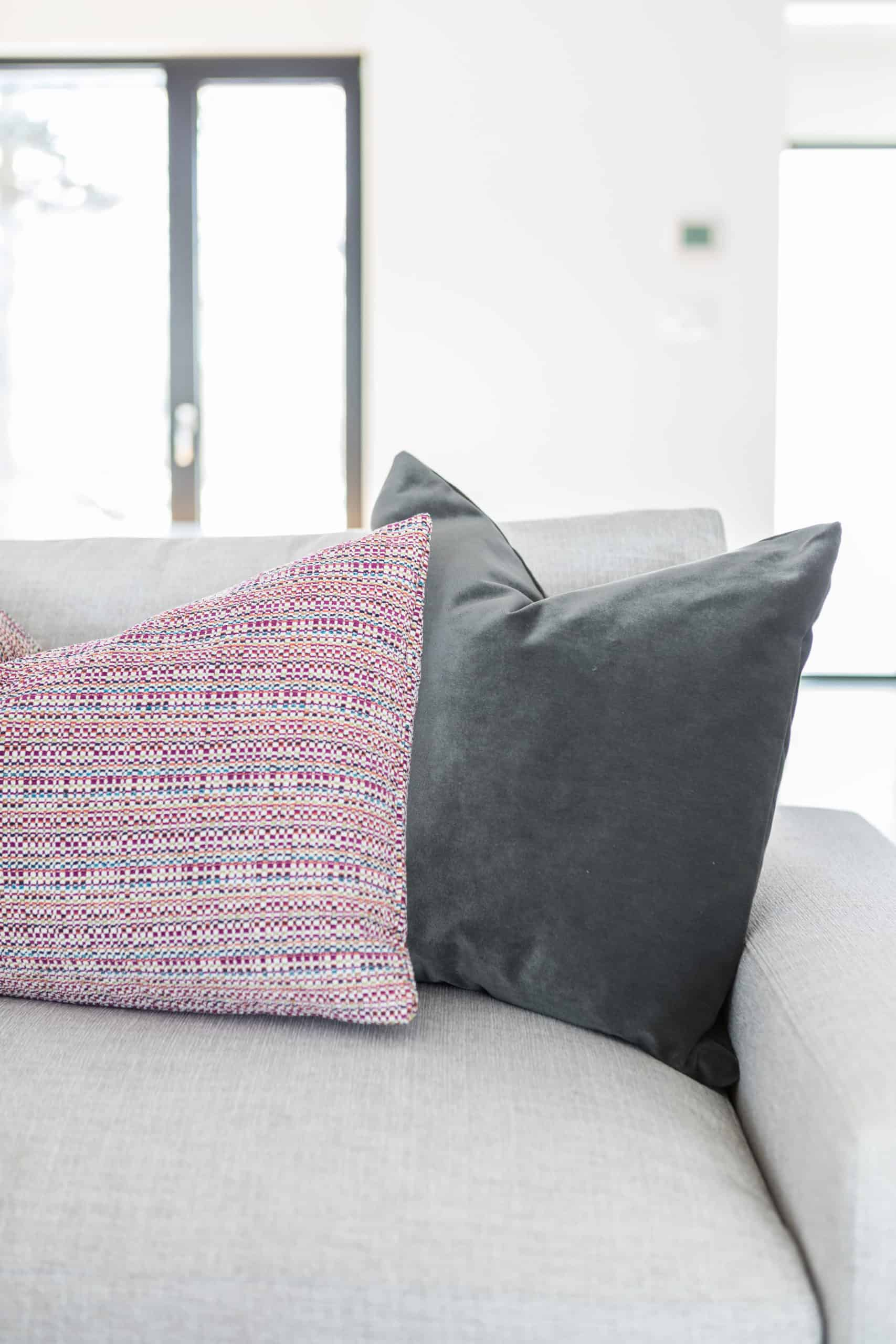 Pink and black pillow on a white couch