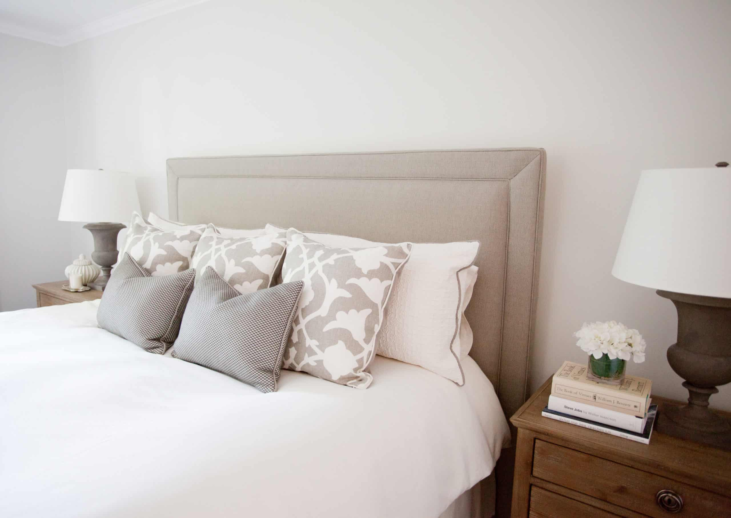 Array of white and grey pillows on a bright white bed