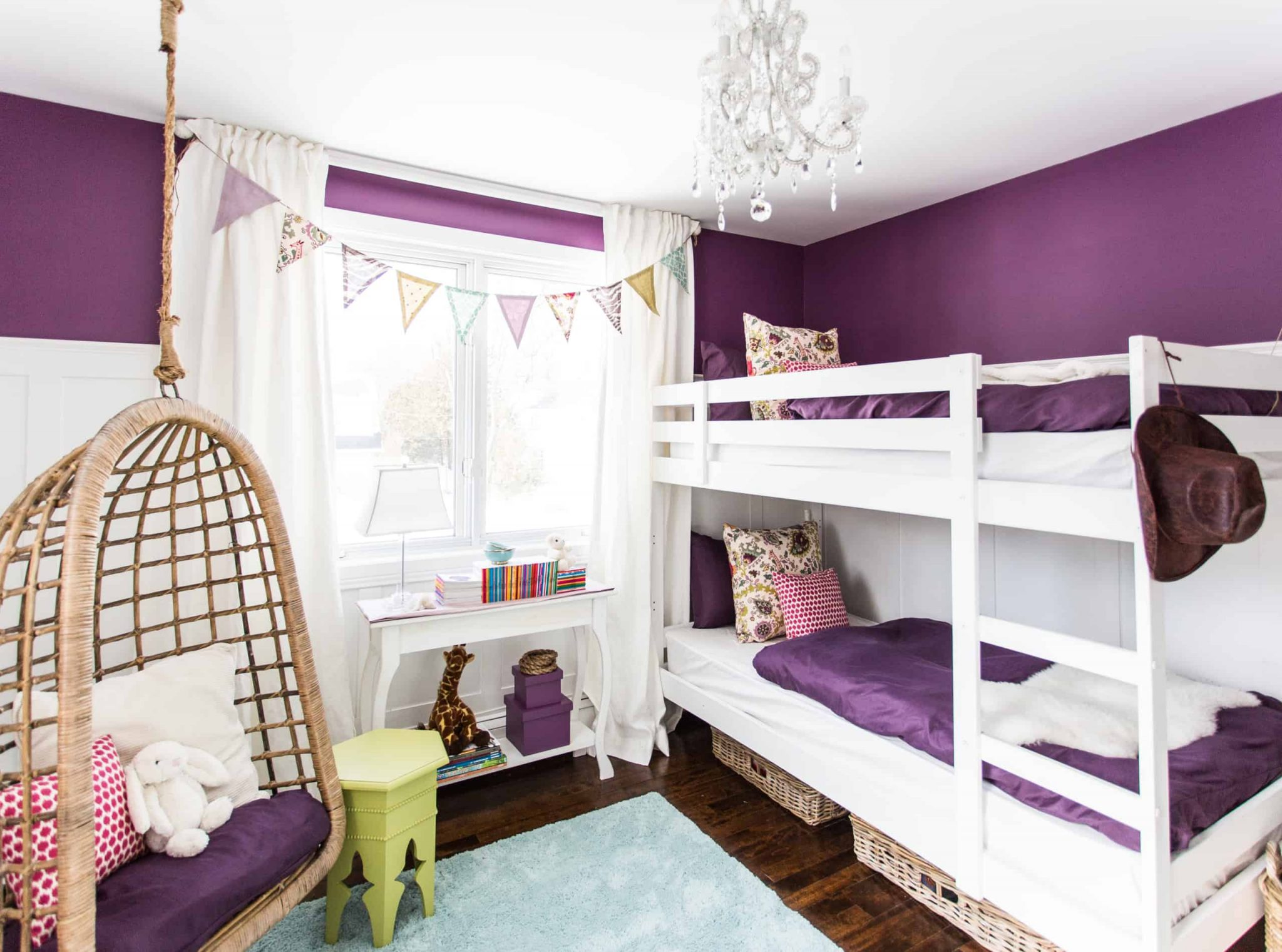 White and purple bunk beds inside a purple themed bedroom