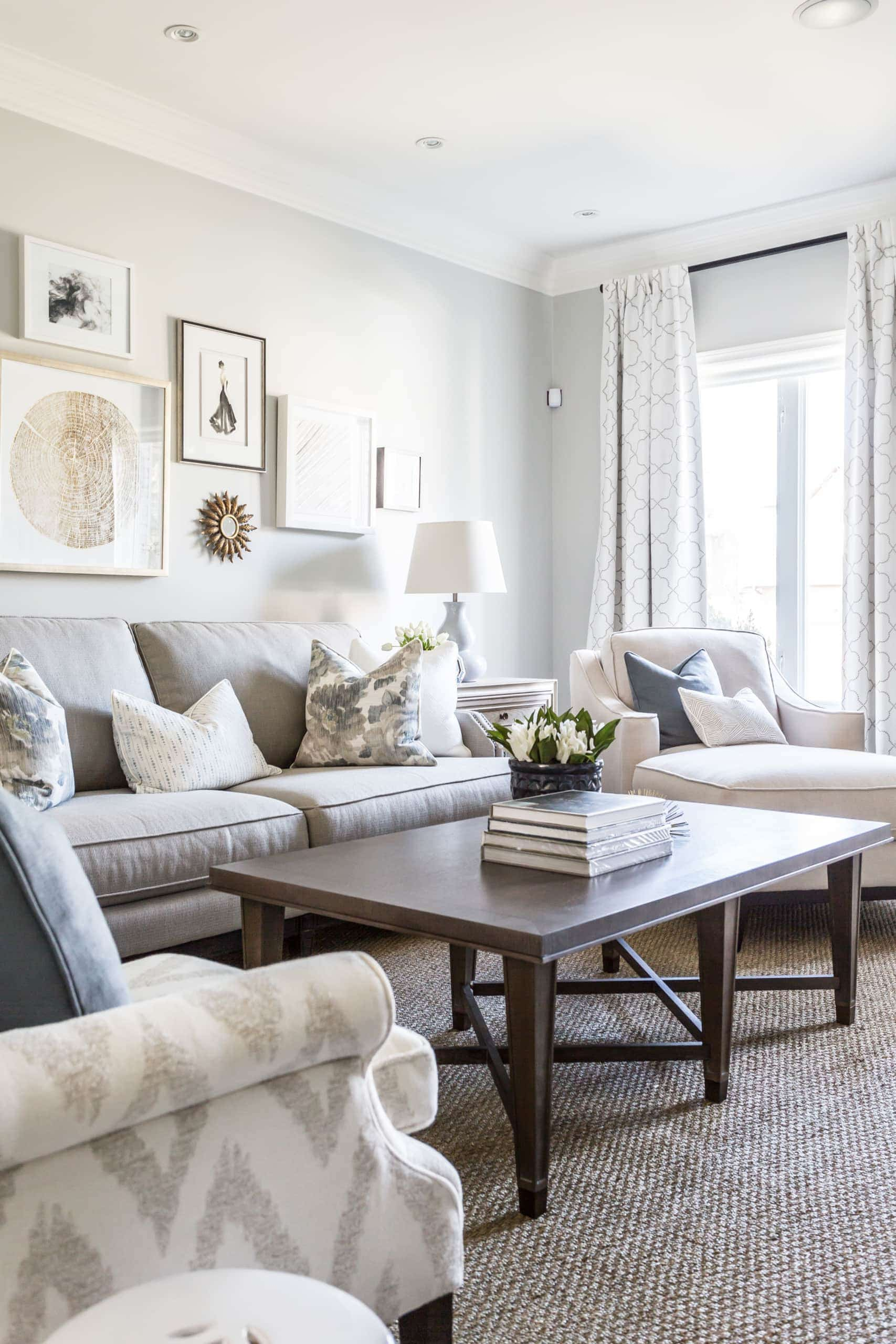 Bright, white living room with various pictures on the wall