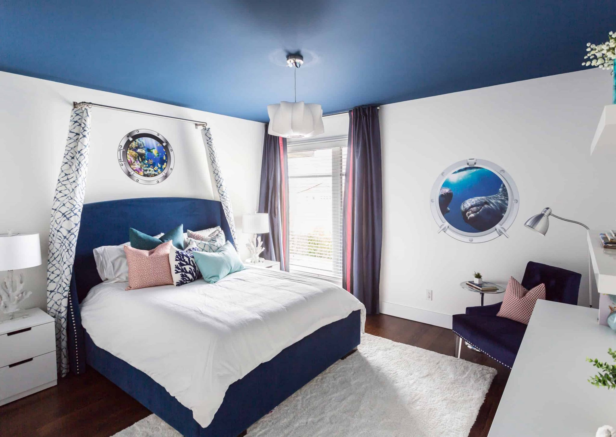 Blue and white bedroom with a window next to the bed