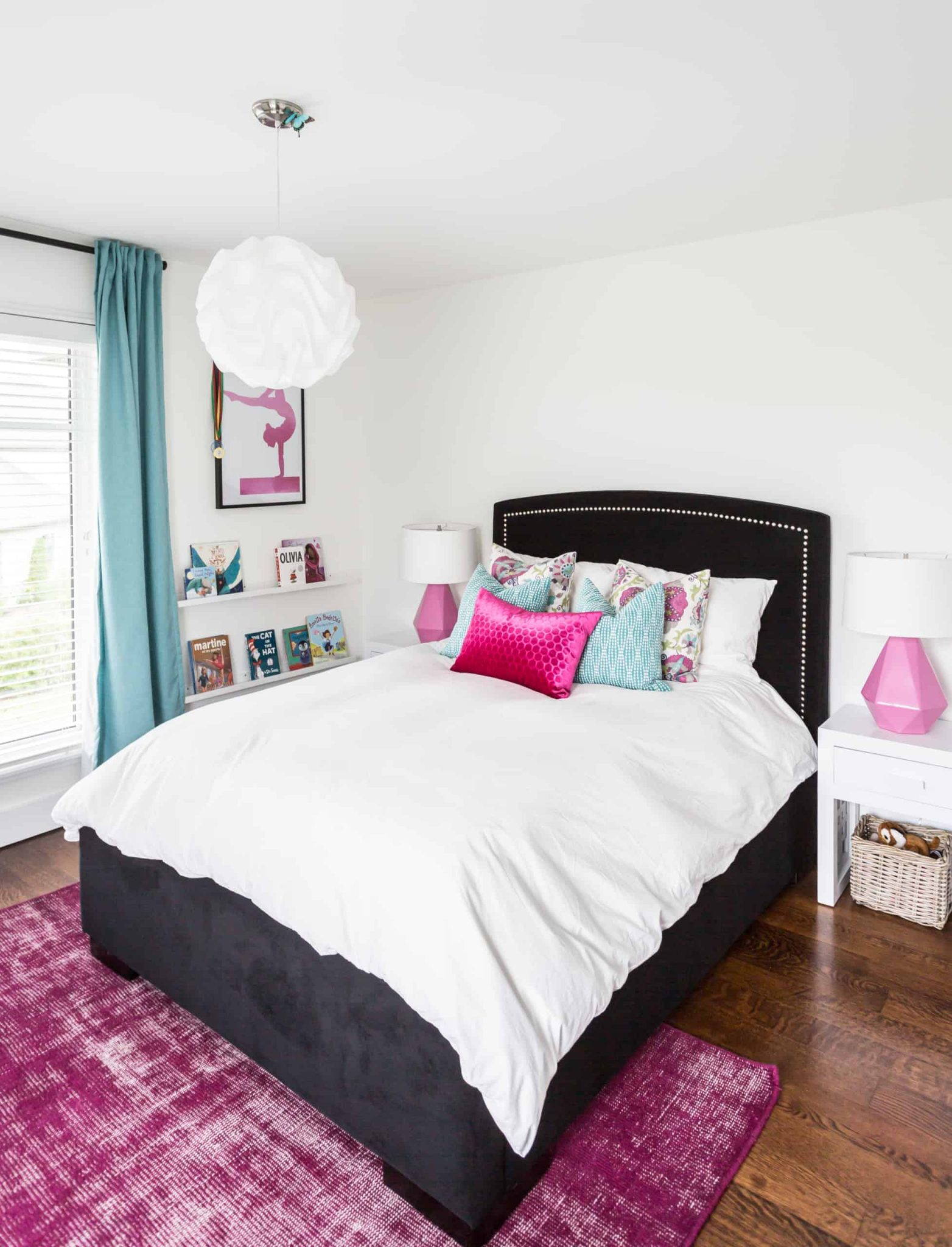 Black bed with colorful pillows and white blankets on it