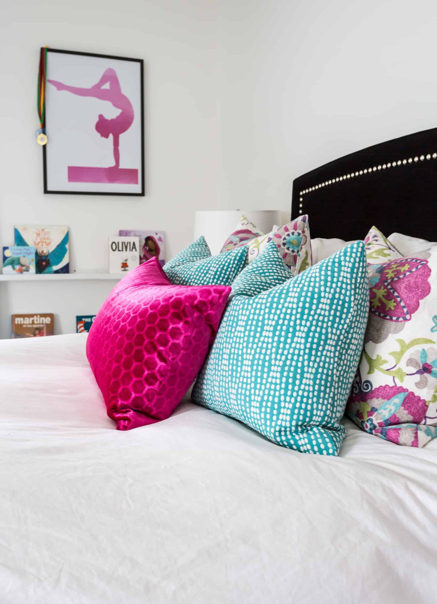 Array of different colored pillows on a white bed