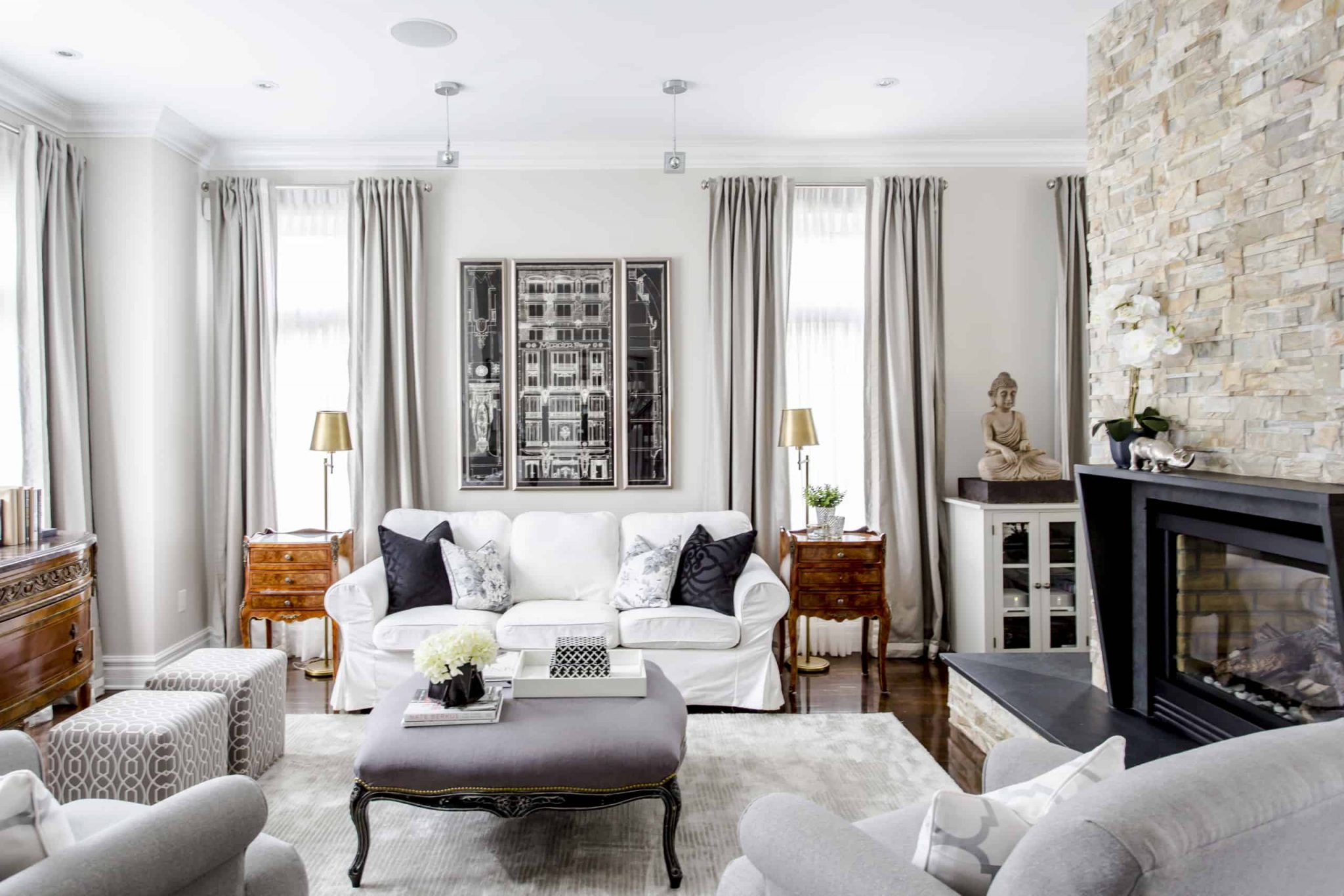 Modern living room containing a bright white couch with a picture above it