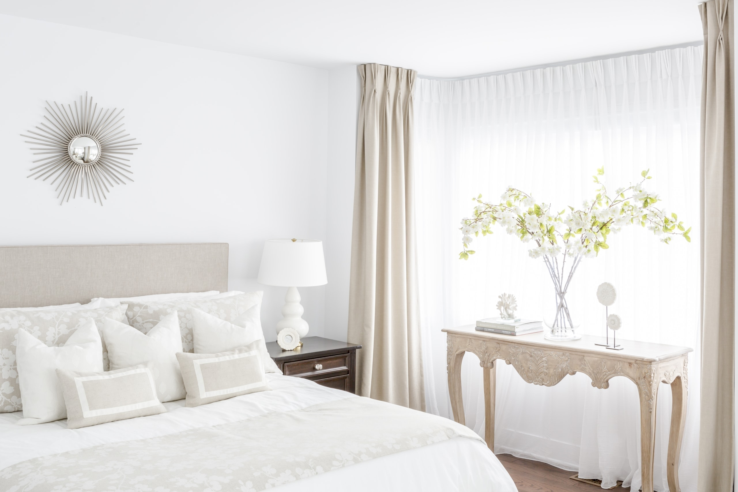 Bright white bed and pink table against the wall inside the master bedroom