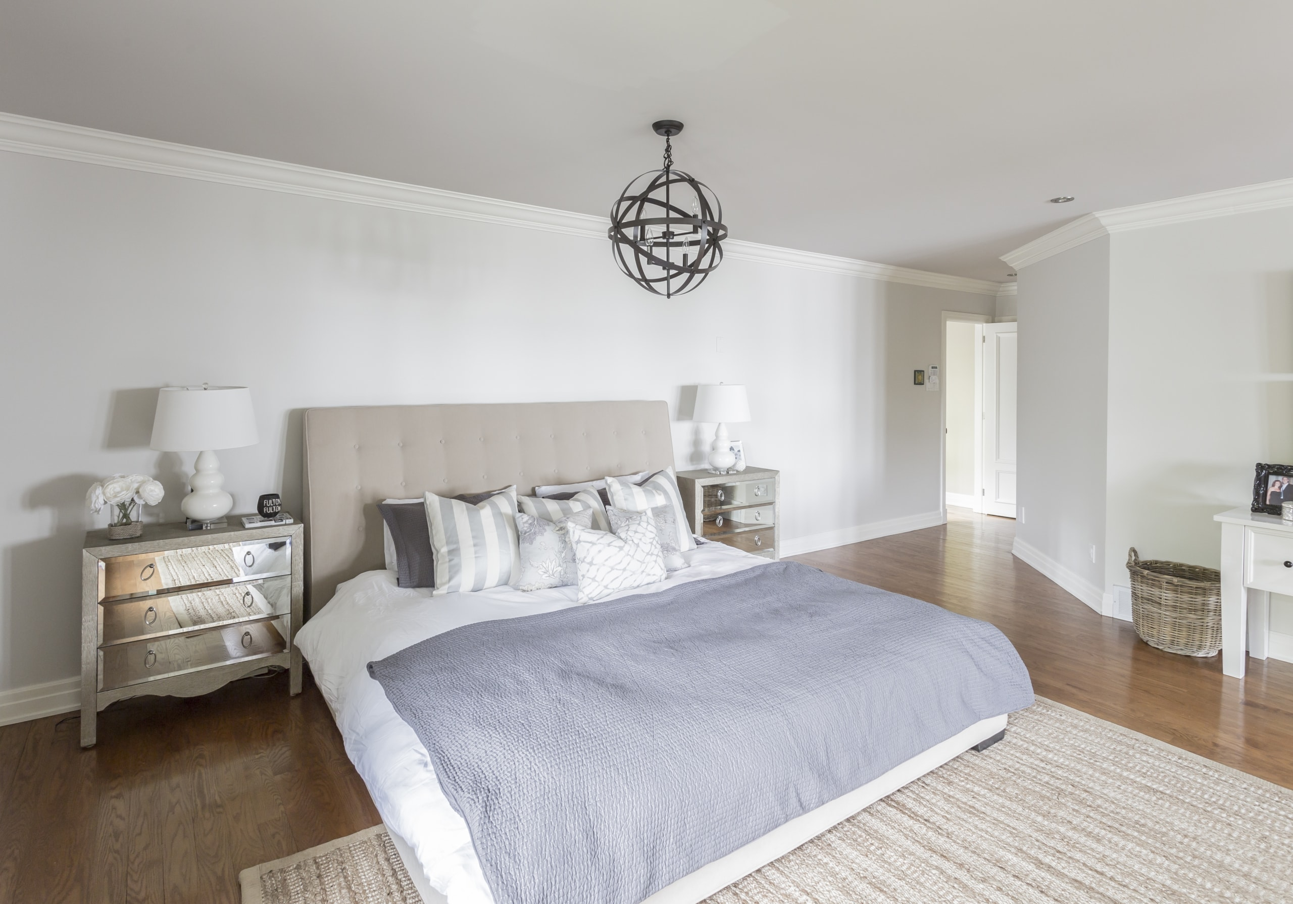 Large bed with a small, dark, spherical chandelier above it