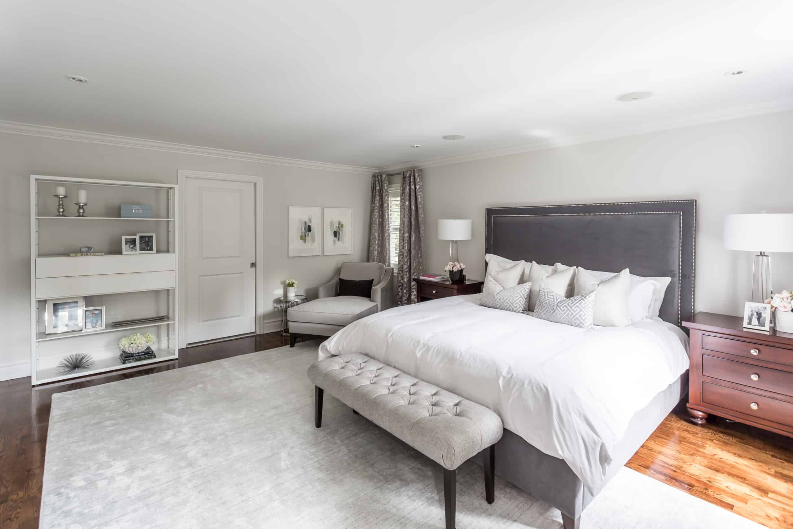 Large, modern master bedroom containing a large gray carpet
