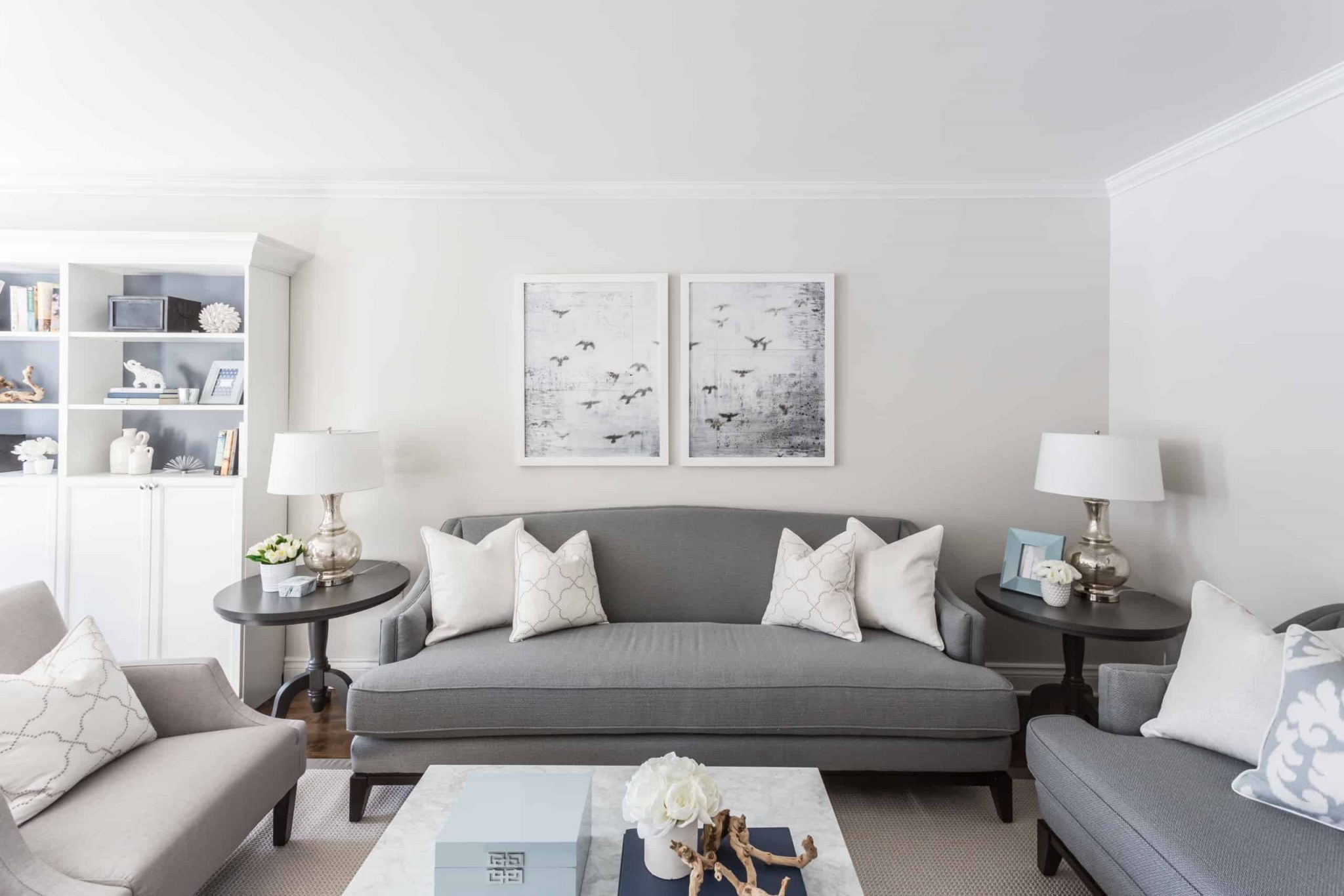 Two pictures above gray couch